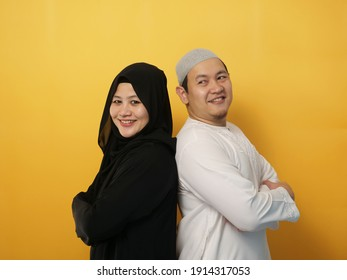 Portrait of happy Asian muslim couple smiling, husband and wife standing leaning on each other back to back, family concept