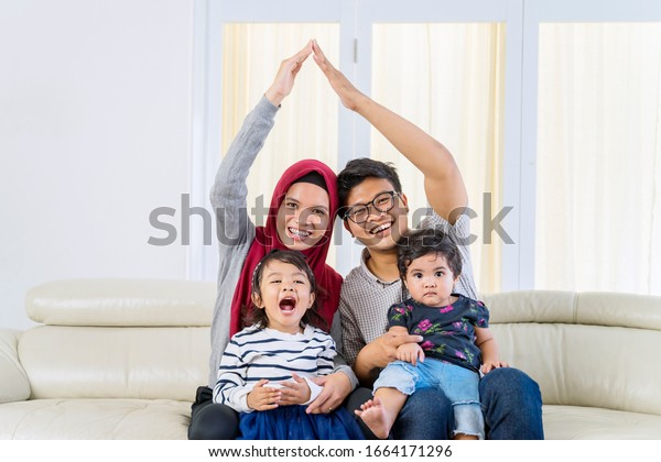 Portrait of happy Asian muslim family smiling at camera, while doing heart symbol pose on a couch in their living room