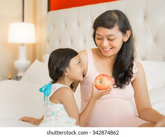 Portrait of Happy Asian Pregnant Mother with Little Girl Offering Healthy Apple
