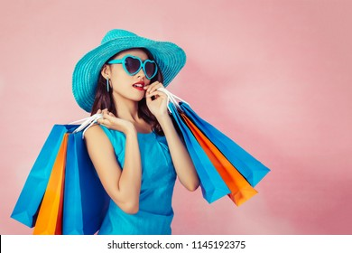 Portrait of a happy Asian pretty girl holding shopping bags  away isolated over pink background,colorful shopping concept.