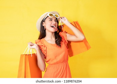 Portrait of a happy Asian pretty girl holding shopping orange bags away isolated over yellow background,colorful shopping concept.