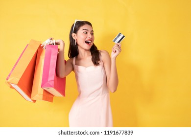 Portrait of a happy Asian pretty girl holding shopping bags while Hold Credit Cards and sunglasses looking away isolated over yellow background,colorful shopping concept.