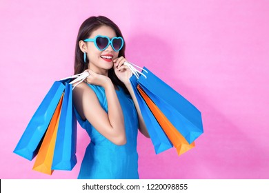Portrait of a happy Asian pretty girl holding shopping blue bags away isolated over pink background,colorful shopping concept.