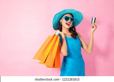 Portrait of a happy Asian pretty girl holding shopping bags while Hold Credit Cards and sunglasses looking away isolated over pink background,colorful shopping concept.