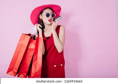 Portrait of a happy Asian pretty girl holding shopping bags while Hold Credit Cards and sunglasses looking away isolated over pink background,colorful shopping concept,christmas theme.