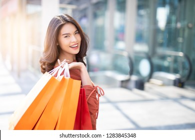 Portrait of a happy Asian pretty girl holding shopping bags background shopping mall concept.