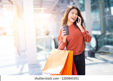 Portrait of a happy Asian pretty girl holding shopping bags while using smartphone background shopping mall concept.