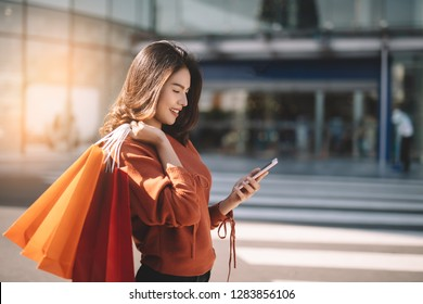 Portrait of a happy Asian pretty girl holding shopping bags while looking smart phone background shopping mall concept.