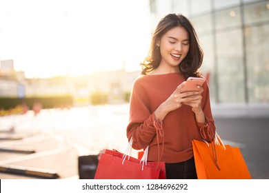 Portrait of a happy Asian pretty girl holding shopping bags while looking at smart phone background shopping mall concept.