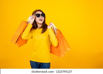 Portrait of a happy Asian pretty girl holding shopping orange bags looking away isolated over yellow background,colorful shopping concept.