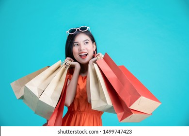 Portrait of a happy Asian pretty girl holding shopping bags look at away isolated over background,colorful shopping concept.