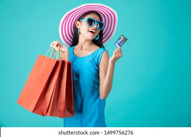 Portrait of a happy Asian pretty girl holding shopping bags while Hold Credit Cards looking away isolated over blue background,colorful shopping concept.