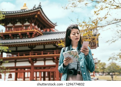 portrait of happy asian tourist searching information on line in smart phone and paper map guidebook on vacations in kyoto japan. nijo castle byodo in standing in background under sunshine in summer.