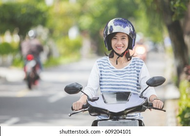 portrait of happy asian woman riding on motorbike in city street