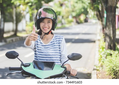portrait of happy asian woman riding on motorbike in city street and showing thumb up