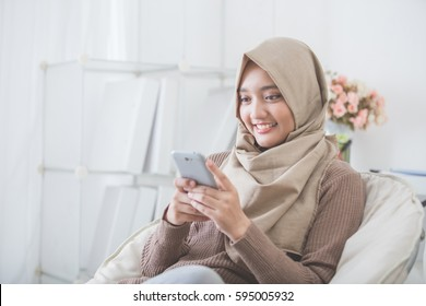 portrait of happy asian woman using mobile phone while sitting on a couch