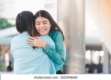 Portrait of happy asian women hugging each friend outdoor city background