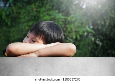 Portrait of Happy Asian young boy peeking over on a cement fence.Smile of a little kid spending a time on sunny summer day.Family,Children,Sibling,Weekend Concept.