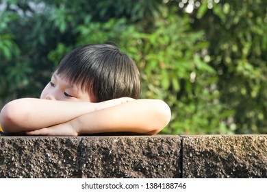 Portrait of Happy Asian young boy peeking over on a wall fence.