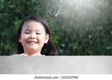 Portrait of Happy Asian young girl peeking over on a cement fence.Smile of a beauty little kids spending a time on sunny summer day.Family,Children,Sibling,Weekend Concept.