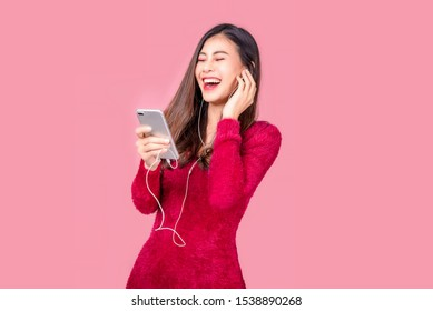 Portrait of a happy Asian young women using mobile phone isolated over pink background