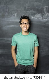 Portrait of a happy Asian/Chinese man standing next to a blackboard.