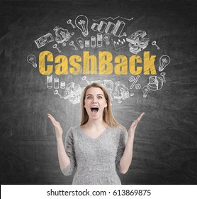 Portrait of a happy or astonished blond woman screaming while standing near a chalkboard with a yellow and white cash back sketch.