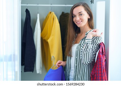 Portrait of happy attractive brunette woman choosing outfit from wardrobe closet with stylish clothes and home stuff