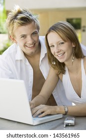 Portrait of a happy attractive couple sitting at the backyard table and using laptop