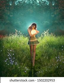 portrait happy Attractive cute fashion woman holds moon in hands. princess universe short dress hugs luminous planet. Walk dream. Green evening summer forest. backgraund   stars park outdoor grass fog