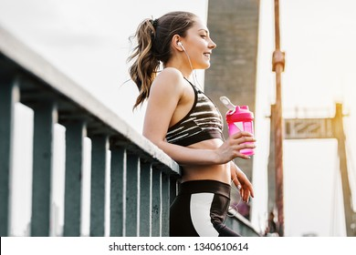 Portrait of happy attractive fitness girl in stylish sportswear drinking water from shaker while standing on bridge. Beautiful slender sports woman listening to music and smiling. Workout outdoors