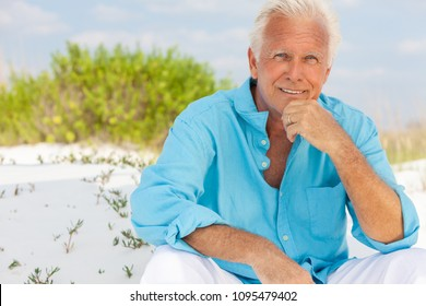 Portrait of a happy attractive handsome senior man sitting down outside on a beach and smiling