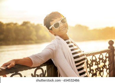 Portrait of a happy attractive mature senior woman 50 years old at sunset