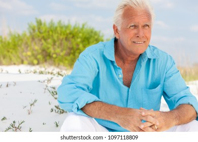 Portrait of a happy attractive thoughtful handsome senior man sitting down outside on a beach and smiling