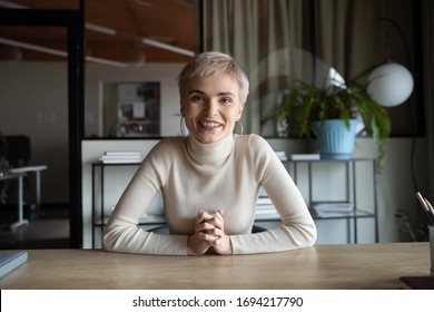 Portrait of happy attractive young businesswoman with short haircut sitting at table, looking at camera. Web cam view skilled female worker holding video call meeting with partners or client from