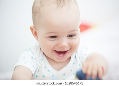 Portrait of a happy baby boy (1 year old) playing on floor in children's room.