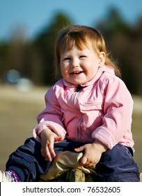 portrait of happy baby girl in park