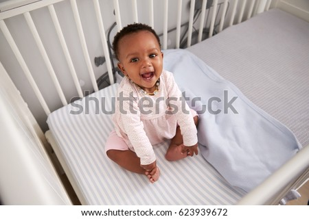 Portrait Of Happy Baby Girl Playing In Nursery Cot