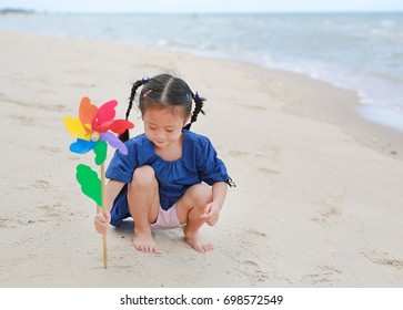 Portrait of happy baby girl with toy windmill on the beach
