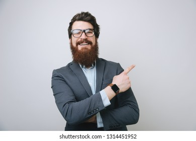 Portrait of a happy bearded businessman in eyeglasses pointing finger away over gray background