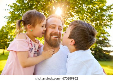 Portrait of happy bearded father spending time with son and daughter in summer park. Family embracing and talking