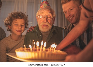 Portrait of happy bearded granddad blowing out candles on cake. Positive concept