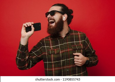 Portrait of happy bearded hipster man singing and listening to music with cell phone and wireless earphones isolated over red wall