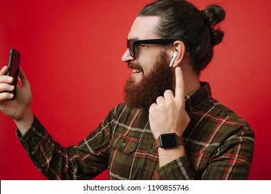 Portrait of happy bearded hipster man using phone and listening music at airpods