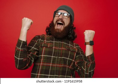 Portrait of happy bearded hipster man celebrating succes over red background