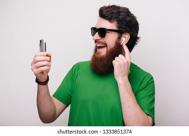 Portrait of happy bearded hipster man wearing sunglasses using phone and listening music at airpods