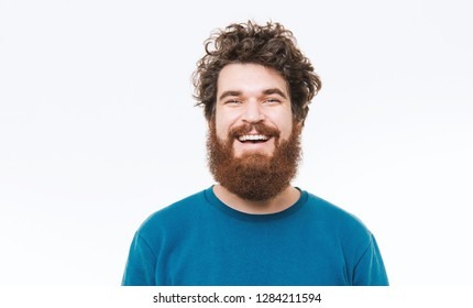 Portrait of happy bearded man in blue pullover smiling at camera