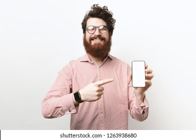 Portrait of happy bearded man with curly-hair pointing to white screen of his smartphone, wearing glasses