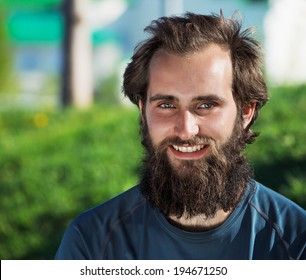 Portrait of happy bearded man on a green park background