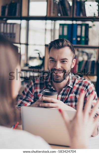Portrait of happy bearded manager drinking coffee and talking with colleague